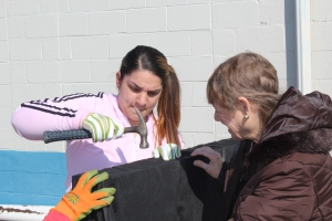 Connecticut River Academy student Rachael Koelsch hammers a cloth onto a pallet, which will serve as a base for a vertical vegetable garden. Goodwin College Webmaster Sandy Pearce instructed Rachael and other students on the process.