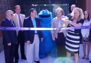 Jenna Tenore, Director of the Goodwin College Early Childhood magnet School, cuts the ribbon on the new school. From left to right: State Rep. Henry Genga, East Hartford School Superintendent Nathan Quesnel, State Center Gary LeBeau, Cookie Monster, East Hartford Mayor Marcia Leclerc, State Education Commissioner Stefan Pryor, Tenore, and Goodwin College Director of Child Study Lori Blake.