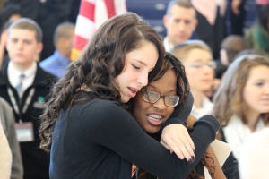 Ninth graders Saige Grace-Lange and Nakia Junor share a hug as they celebrate a permanent home for their school.