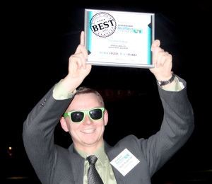 """Piotr Krzemien displays Goodwin's """"Best Places to Work"""" award for 2014."""